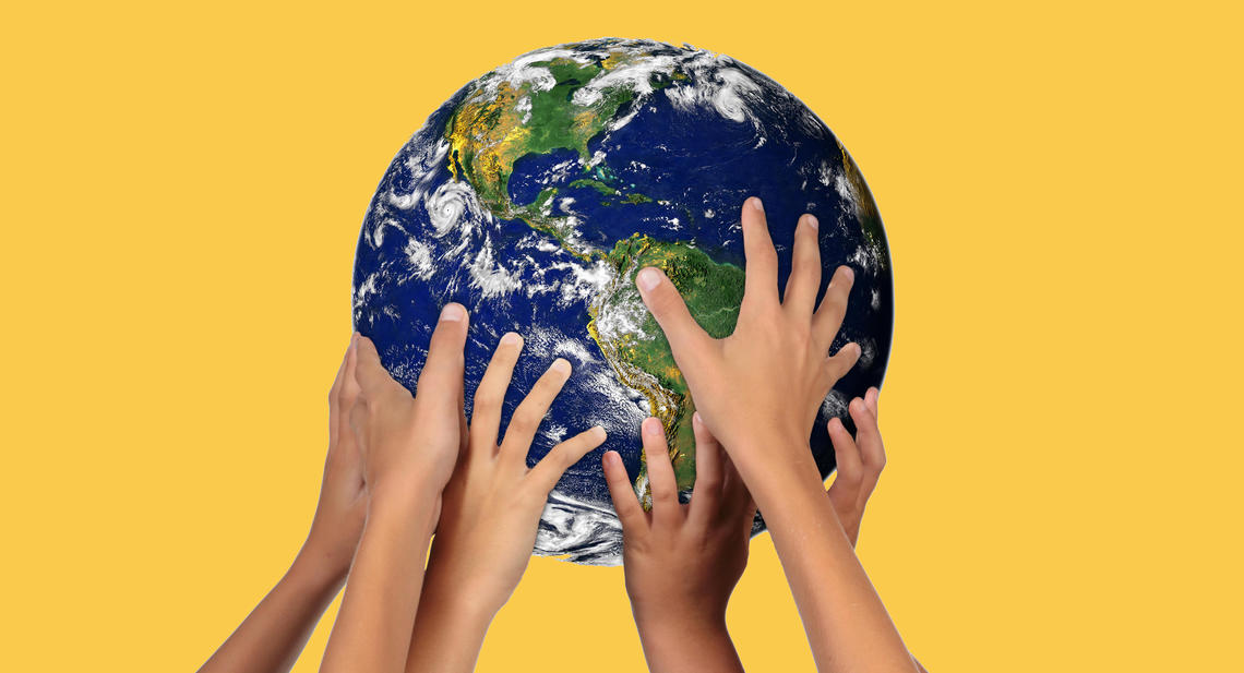 Children's hands holding up a globe